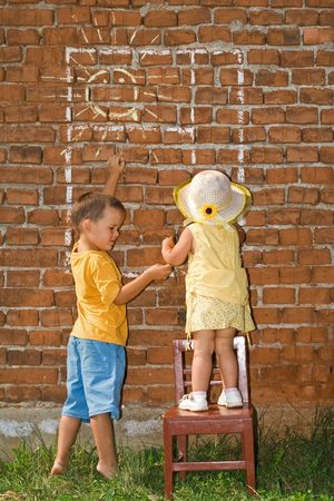 Kids drawing sunny window to a brick wall - in bright summer afternoon lights photo