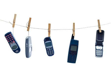phone button: Verouderde communicatietechnologie - geïsoleerde oude mobiele telefoons opgehangen voor het drogen Stockfoto