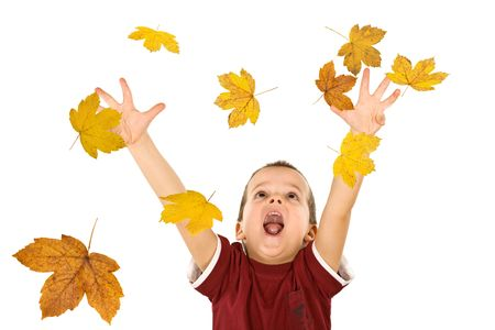 Happy boy shouting and reaching out for the falling autumn leaves - isolated, without motion blur photo