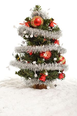 Small decorated christmas tree in artificial snow - isolated photo