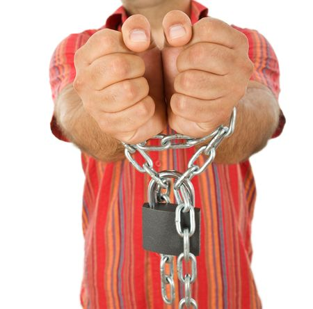 Man hands in massive chains with padlock - closeup Stock Photo - 6296439