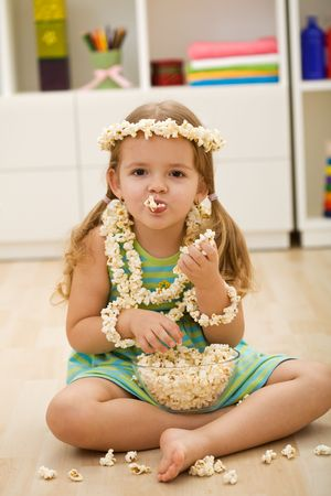 bowls of popcorn: Happy little girl eating popcorn sitting in her room Stock Photo