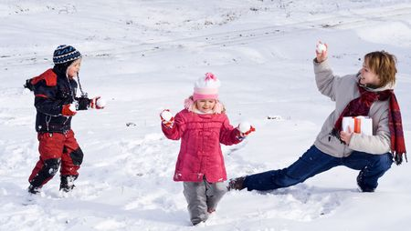 Happy kids and woman playing in the first snow of winter photo