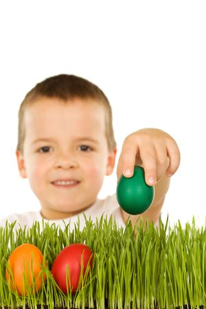 Boy putting colorful easter eggs in the grass - isolated photo
