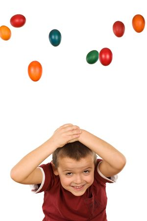 Boy with falling easter eggs protecting his head - isolated photo