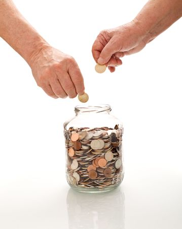 Senior hands collecting coins in a glass jar - saving for retirement concept, isolated photo