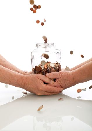 Elderly hands holding jar catching falling coins - successful investment of the retirement fund concept photo