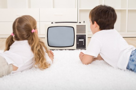Kids watching old television set laying on the floor Stock Photo