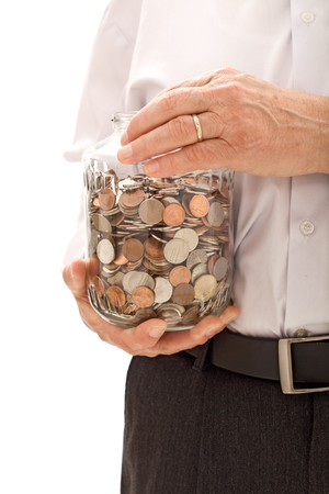 Senior hands holding jar with coins - saving for retirement concept photo