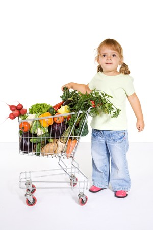 Happy healthy little girl with vegetables in a shopping cart looking surprised - partly isolated photo