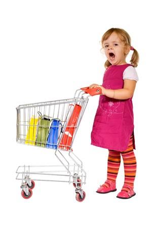 ni�o empujando: Ir de compras es aburrido - poco chica enorme permanente por un carro con coloridos bolsas  Foto de archivo