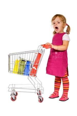 yawning: Shopping is boring - little girl yawning standing by a cart with colorful bags