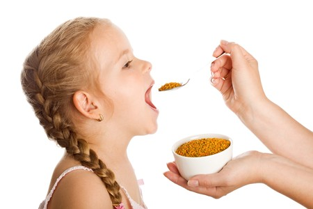 remedies: Little girl taking pollen granules with spoon - traditional remedies concept