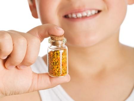 Little boy holding small bottle of pollen - natural remedies concept, closeup photo