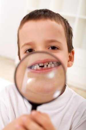 Boy with magnifier showing his first lost tooth - closeup photo