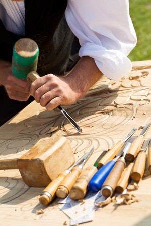 Artesano tradicional tallado en madera con motivos florales