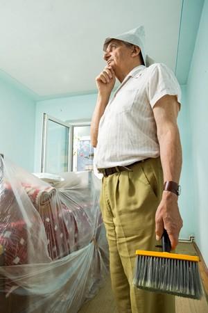 redecorating: Senior man thinking about redecorating, holding large paintbrush