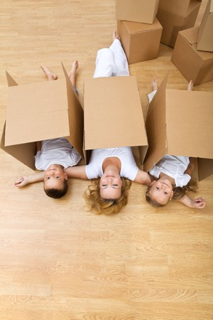 Family playing with carboard boxes in their new home photo