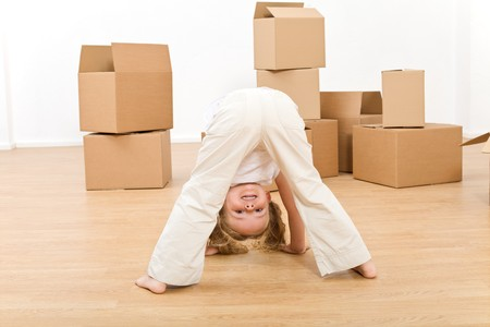 Little girl playing in her new home having fun among boxes photo