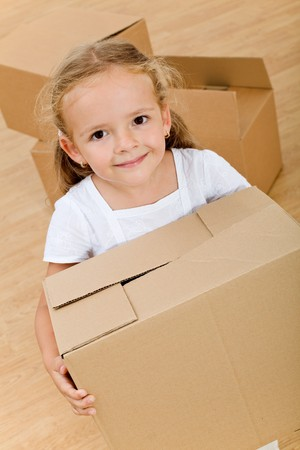 Little girl moving into a new home with cardboard box  - top view photo
