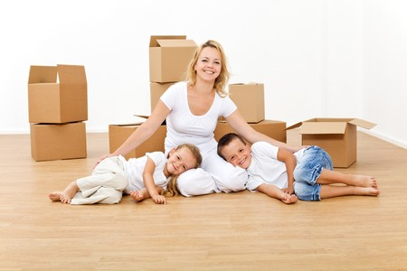 Woman with kids in their new home relaxing on the floor photo