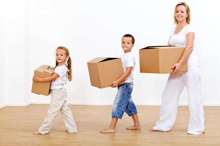 Family moving in to a new home carrying cardboard boxes Stock Photo