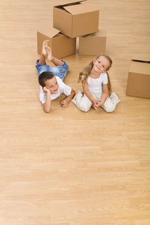 new home: Kids on the floor in their new home - top view, copy space