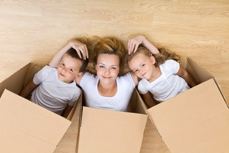 Happy family unpacking in their new home - relaxing on the floor photo