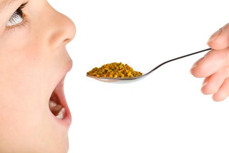 granules: Boy taking traditional medicine - pollen granules in a spoon, isolated Stock Photo