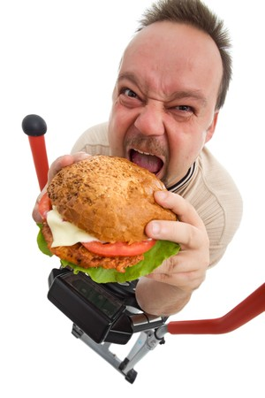 fail: To hell with exercises - man eating big hamburger on elliptical trainer device - isolated