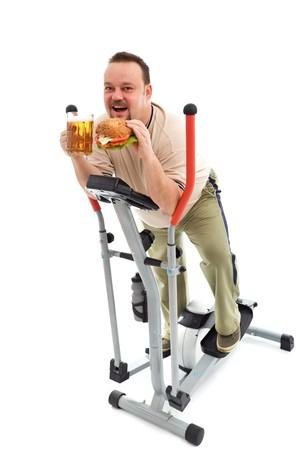 sedentario: Me encanta ejercicio - hombre con gran hamburguesa y cerveza en equipos de ejercicio  Foto de archivo
