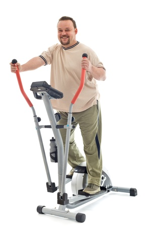 elliptical: Confident overweight man exercising on elliptical trainer - isolated Stock Photo