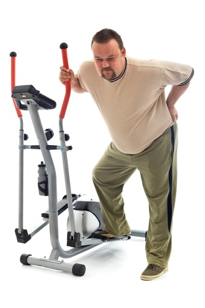 Man holding his aching back leaning on exercising device - isolated Stock Photo