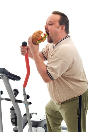 trainer device: Man with gymnastic trainer device eating a large hamburger - isolated