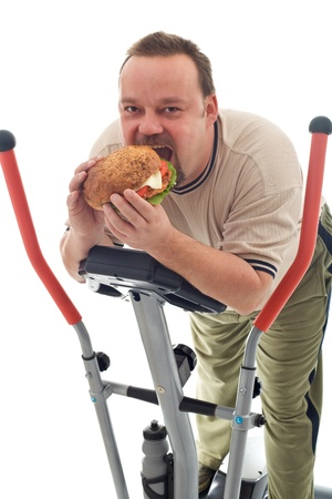 sedentary: Man eating huge hamburger while resting on a trainer device - isolated Stock Photo