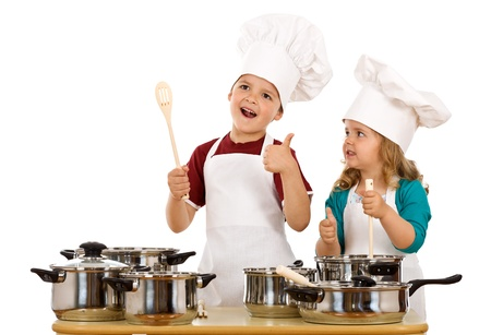 children cooking: Happy satisfied chef and his aid - kids with cooking utensils, isolated Stock Photo