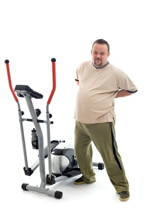Overweight young man stretching and holding his aching back near a trainer device - isolated photo