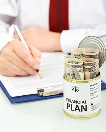 Business man making financial plan with an opened can of dollars - conceptual, closeup Stock Photo - 8798209