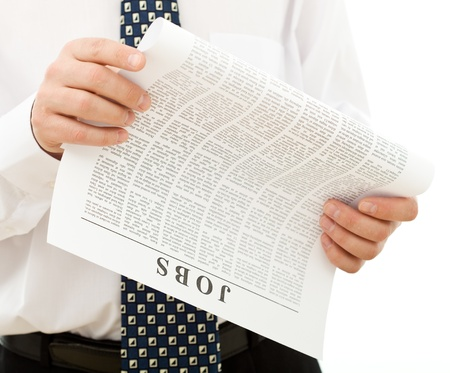 job advertisement: Man in shirt and tie looking for job reading a paper with clasified ads - closeup, isolated