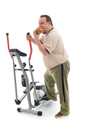 Overweight man eating a large hamburger standing by an exercising device - fittness fail concept isolated