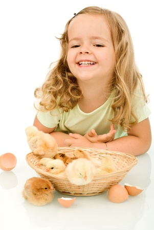 Happy little girl with her spring fluffy chickens in a basket - isolated, closeup photo