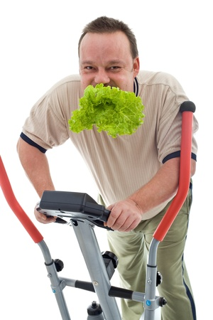 Power slimming concept with overweight man on exercise machine eating fresh green salad - isolated Stock Photo - 9060520