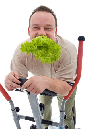 Power slimming concept - man exercising and eating healthy fresh food, isolated Stock Photo - 9060519