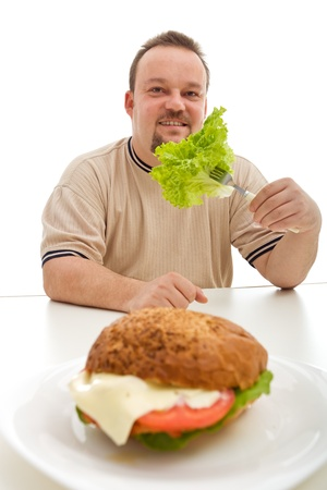 Healthy diet choices concept with overweight man eating lettuce instead of burger Stock Photo - 9060521