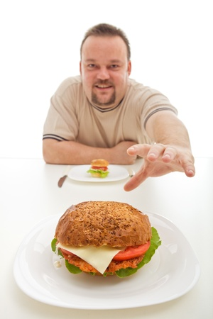 bigger: Man with small hamburger reaching for a bigger one - diet choices concept