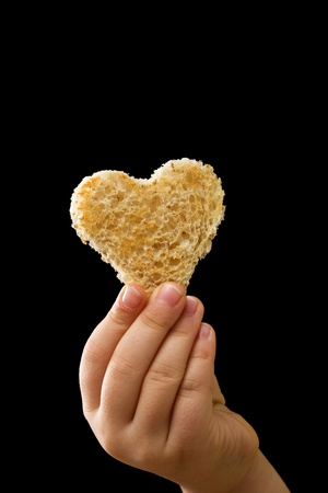 A piece of bread offered with love - isolated on black Stock Photo - 9061484