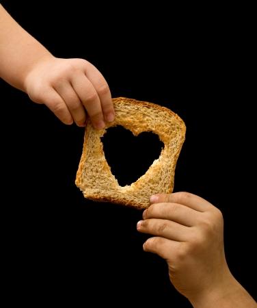 Condivisione di cibo con i bisognosi - kids le mani con una fetta di pane Archivio Fotografico