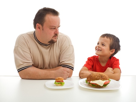 humorously: Man and young boy humorously rival over food