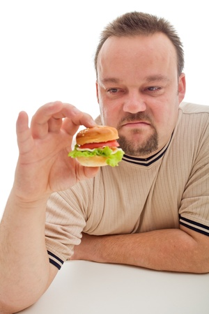 disappointed: Man not happy about the size of his hamburger - size matters in diet too Stock Photo