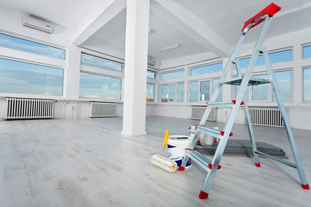 Newly renovated generic empty office space with leftover materials and ladder in foreground Stock Photo